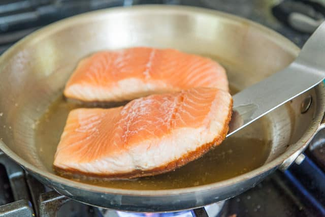 Lifting Up The Salmon Filet To Show Crispy Skin