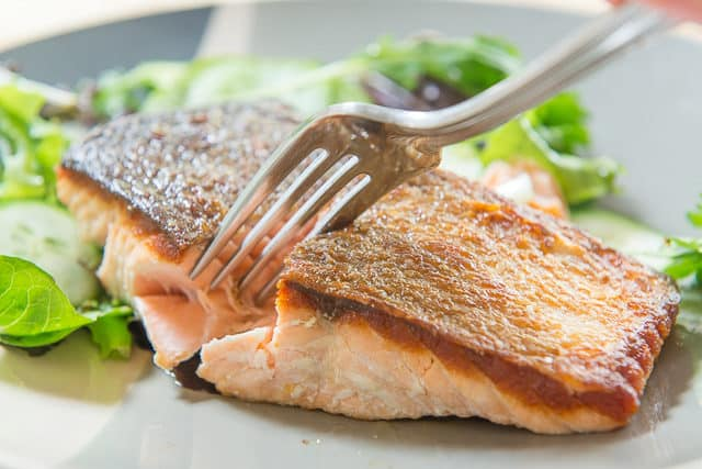 Seared Salmon - Served Over a Bed of Greens On Plate with Fork Showing Moist Interior