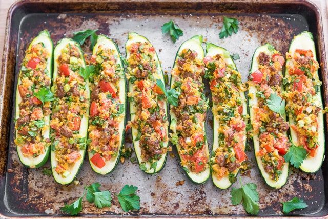 A half sheet baking pan with eight Italian Sausage Stuffed Zucchini Boats on top and sprinkled with chopped parsley leaves