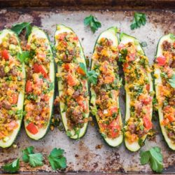 Sausage Stuffed Zucchini Lined Up In a Single Layer on a Sheet Pan