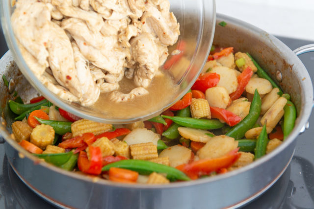 Pouring Partially Cooked Chicken Into Skillet with Vegetables