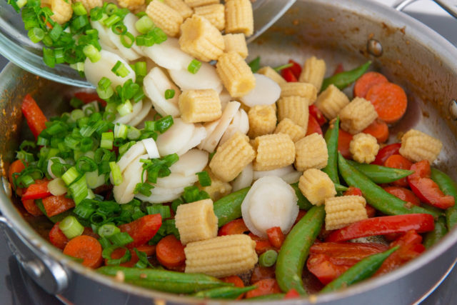 Pouring Baby Corn, Water Chestnuts, and Scallions Into Skillet