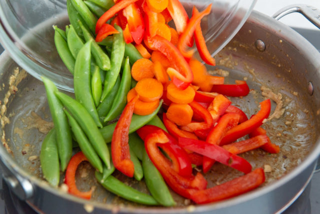 Sliced Bell Pepper, Snap Peas, and Carrots Poured Into Skillet