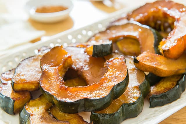 Baked Acorn Squash - Presented in Slices on a White Platter on Wooden Surface