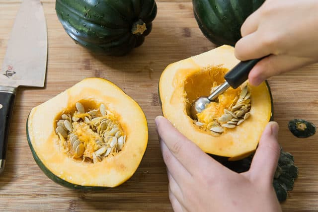 Scooping Seeds Out of Raw Acorn Squash Using Melon Baller