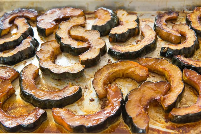 Roasted Acorn Squash Recipe Shown in a Single Layer on Sheet Pan with Caramelized Edges