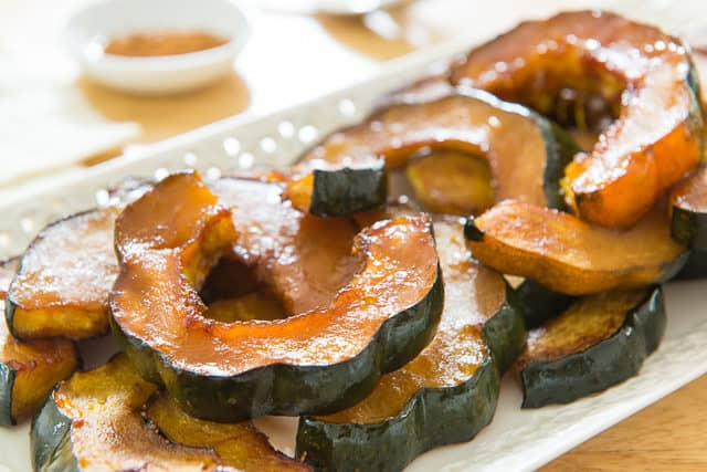 Slices of Acorn Squash Roasted with maple Butter Served On White Platter
