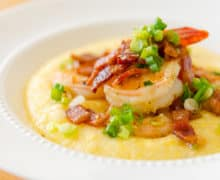 Shrimp and Grits in White Bowl with Scallion Garnish