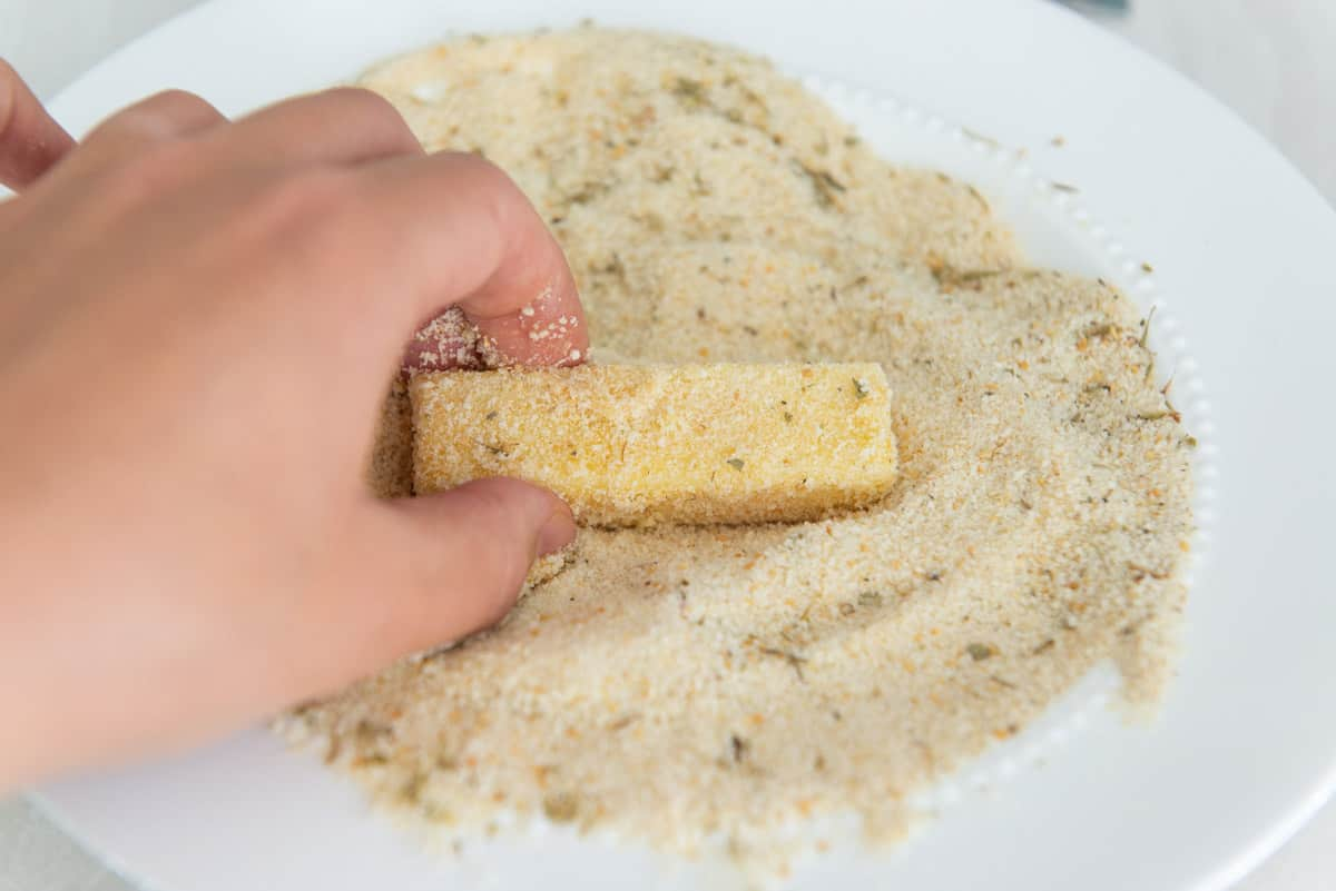 Breading a piece of cheese with dry bread crumbs