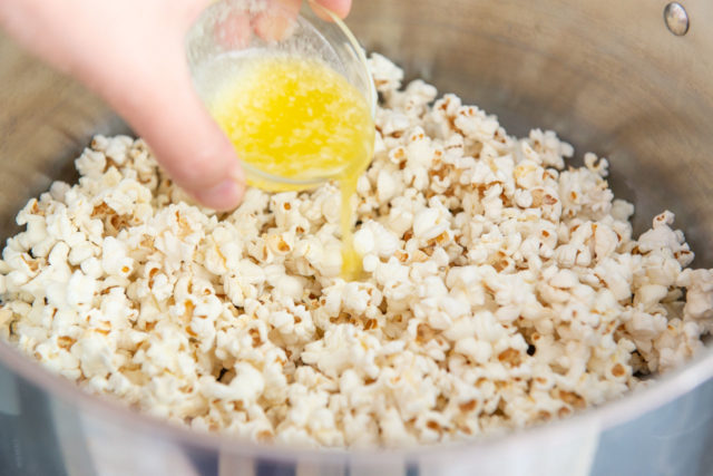 Pouring Butter Over the Freshly Popped Popcorn