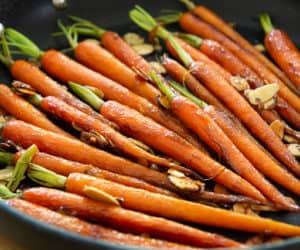A black nonstick pan filled with maple glazed carrots and sliced almonds