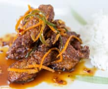 Orange Beef On a Green and White Platter with Orange Rind Strips
