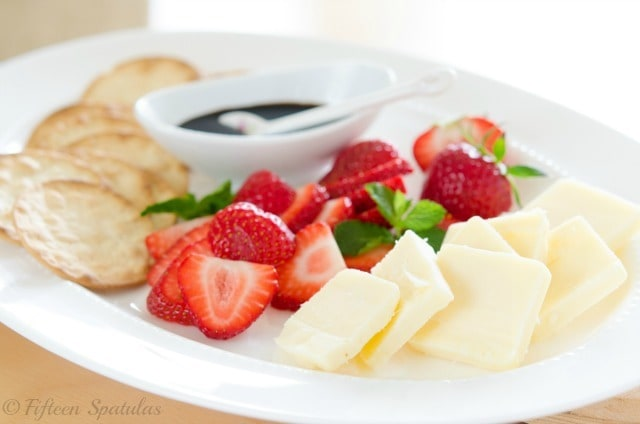 Cheese Pairing Visual Guide: strawberries, mint, aged cheddar, black pepper crackers, balsamic glaze on White Plate