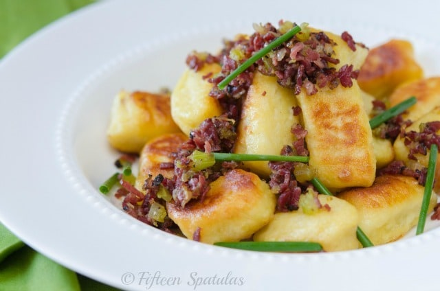 Crispy pan fried gnocchi in white bowl with pastrami and chives