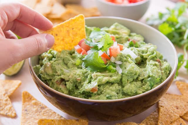 Guacamole Recipe - Served in Brown bowl with Chip Dipping Into It