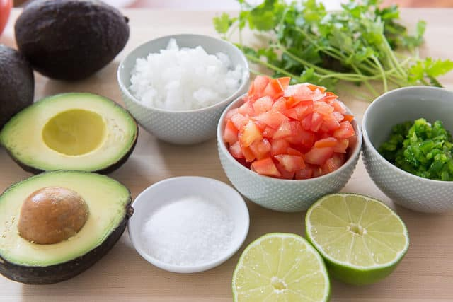 Guacamole Ingredients - On a Cutting board with Avocado, Tomato, Onion, Salt, Cilantro, and Lime