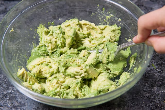 Fork Mashing Avocados in a Bowl
