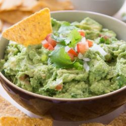 A Bowl of Guacamole with a Chip in It