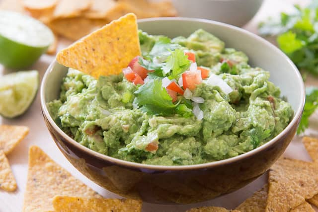 Homemade Guacamole - In a Brown Bowl with Tortilla Chip Dipped