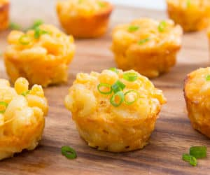 Mac and Cheese Cups Served on Wooden Board with Scallions On Top