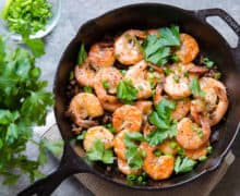 Peel and Eat Shrimp In Cast Iron Skillet with Scallions and Parsley On Top