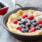 Dutch Pancake Recipe Served in Skillet with Powdered Sugar and Berries On Top