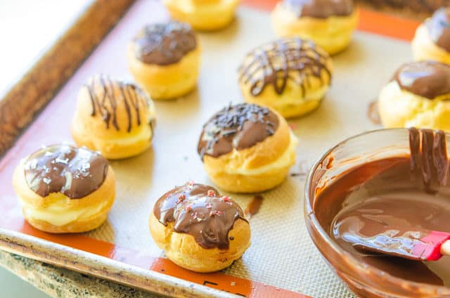Cream Puff Filling Sticking Out of Dough with Chocolate Dip on Top of Silicone Mat