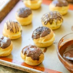 Cream Puffs On a Silicone Mat Filled With Pastry Cream And Chocolate Glazed