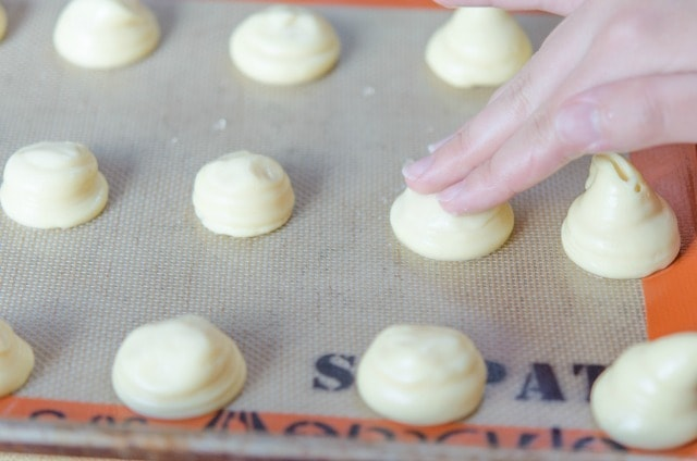 Pressing Down Tops of Piped Choux Dough with Fingertips