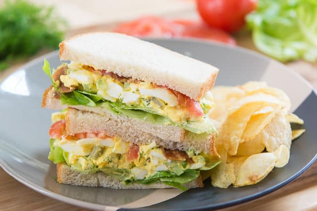 Two Egg Salad Sandwiches Halves Stacked On Top Of Each Other With Side Of Potato Chips