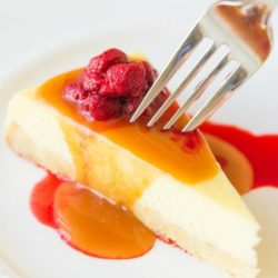 Caramel Cheesecake on Plate with Fork Entering Center of Slice