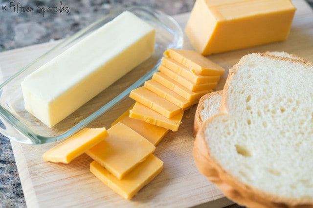 Stick of Butter, Sliced Cheddar Cheese, and White Sandwich Bread on Board