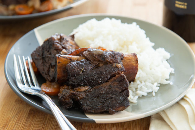 Slow Cooker Beef Short Ribs - Plated with White Rice and a Fork with Wine in Back