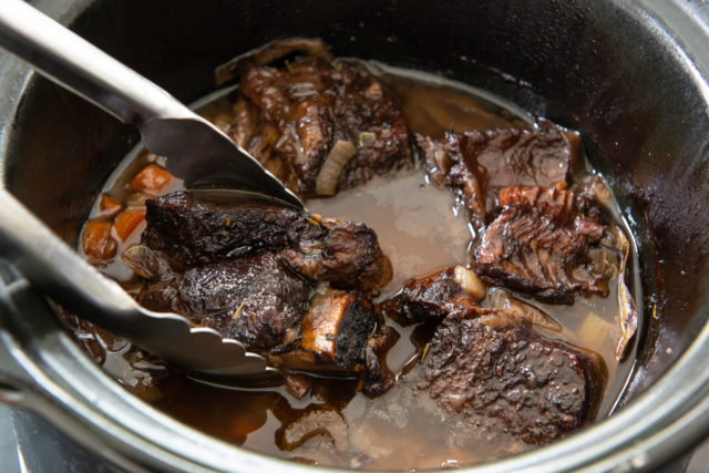 Short Rib Recipe Slow Cooker with Tongs Showing Tenderness of Piece