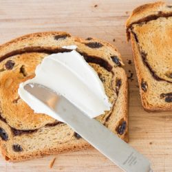 Cinnamon Raisin Bread Being Spread with Butter Using a Knife
