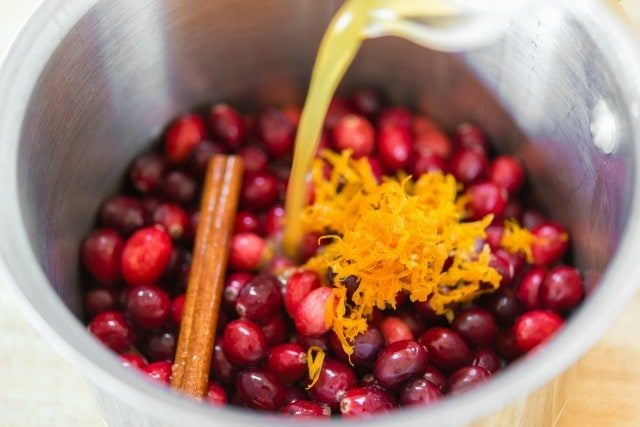 Pouring Orange Juice Into Pan with Cranberries, Orange Zest, and Cinnamon