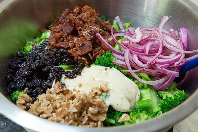 Broccoli Salad with Bacon, Red Onion, Mayonnaise, Raisins, and walnuts Added in Bowl