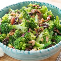 Broccoli Salad In a Blue Bowl with Red Onion and Raisins