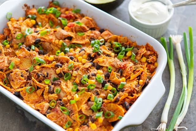 Tex Mex Chicken Casserole Baked in Green Dish with Sour Cream on Side