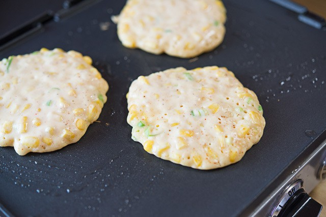 Fried Corn Cakes with Green Onions on Griddle