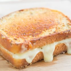 Brie Grilled Cheese Oozing Out Cheese on Cutting Board