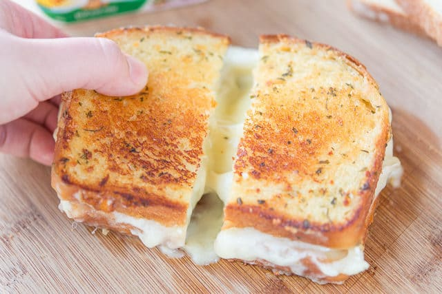 Pulling Apart Brie Cheese Sandwich to Show Gooey Interior