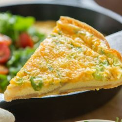 A close up of a slice of Potato Cheddar Frittata