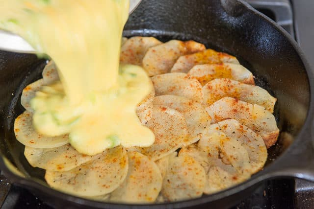 Pouring Egg Potato Frittata Batter in Cast Iron Skillet