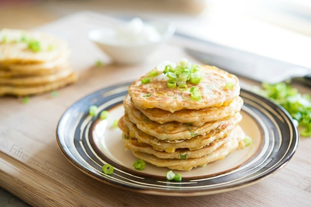 Savory Corn Pancakes - Stacked on a Plate and Garnished with Scallions