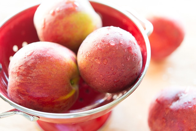 Fresh Peaches in Red Colander
