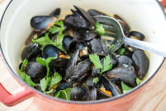 Thai Green Curry Mussels with Slotted Spoon and Herbs