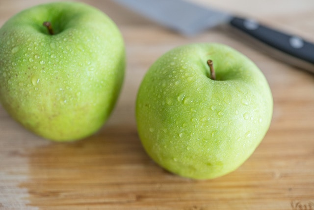 A green apple on top of a wooden cutting board