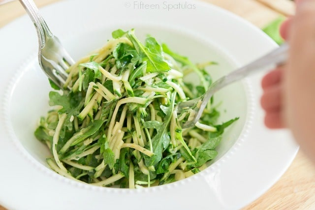 Zucchini Arugula Salad Recipe - Plated in Bowl with Forks Tossing
