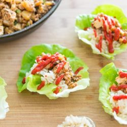 Lettuce Wraps On a Wooden Board with Sriracha Sauce Drizzle